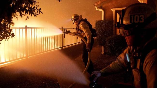 Seorang warga mengaku melihat api menyapu lereng bukit, bergerak melalui rumput kering dan membakar pohon dan semak-semak. (AP Photo/Michael Owen Baker)