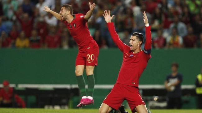 Cristiano Ronaldo lalu mencetak gol kedua Portugal di menit ke-64 lewat tendangan lob yang melampaui jangkauan Anthony Morris. (AP Photo/Armando Franca)