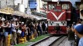 Namun padatnya aktivitas turisme di Train Street membuat jadwal kereta yang lewat terganggu, karena harus menahan laju agar tak membahayakan orang yang ada di sekitarnya. (AFP/Manan Vatsyayana)