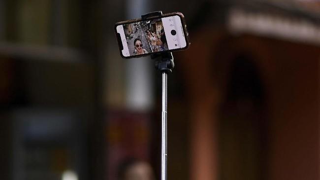 Ponsel berkamera dengan tongkat selfie milik turis di Train Street, Hanoi, Vietnam. (AFP/Manan Vatsyayana)