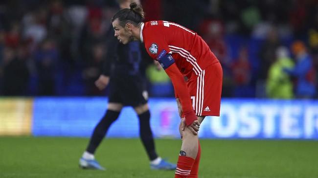 Gareth Bale terlihat mengeluh sakit pada bagian kaki kiri saat laga Wales vs Kroasia. Bale dan Modric berpeluang absen memperkuat Real Madrid melawan Barcelona di El Clasico. (GEOFF CADDICK / AFP)