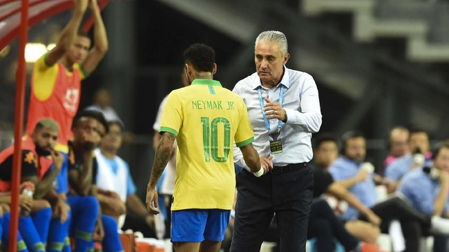 Neymar ditenangkan pelatih timnas Brasil Tite setelah digantikan Philippe Coutinho pada menit ke-12. (Roslan RAHMAN / AFP)