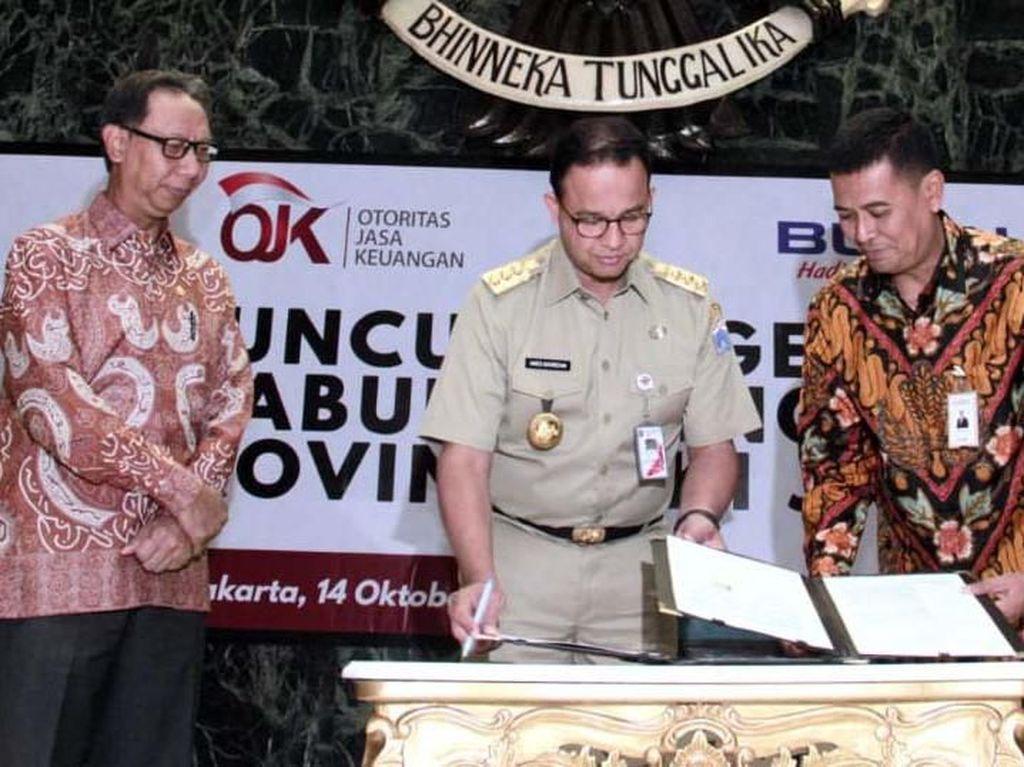 Direktur Bisnis Konsumer BNI Anggoro Eko Cahyo (kanan) dan Gubernur DKI Jakarta Anies Baswedan (tengah) menandatangani nota kesepahaman Terkait Tata Kelola Berbasis Masyarakat yang menandai peluncuran Gerakan Ayo Menabung dengan Sampah, yang turut disaksikan oleh Anggota Dewan Komisioner OJK Tirta Segara (kiri) di Jakarta, Senin (14 Oktober 2019).