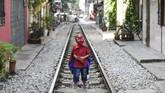 Anak kecil dengan kostum Spiderman berpose di tengah rel kereta Train Street, Hanoi, Vietnam. (AFP/Nhac Nguyen)