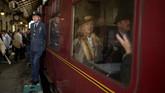 Pengunjung berkostum kuno bersiap melakukan perjalanan dengan kereta uap dalam acara tahunan 'Railway in Wartime' yang diadakan di sepanjang North Yorkshire Moors Railway, di Pickering, utara Inggris pada 12 Oktober 2019. (AFP/ OLI Scarff)