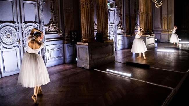 Persembahan berikutnya menampilkan tiga orang penari yang mengenakan rok tutu warna putih, menarikan koreografi kontemporari. (Photo by Martin BUREAU / AFP)