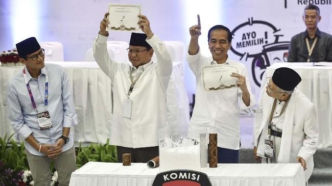 Pasangan Joko Widodo-Ma'ruf Amin dan Prabowo Subianto-Sandiaga Uno menunjukkan nomor urut mereka di kantor Komisi Pemilihan Umum, Jakarta Pusat, Jumat (21/9/2018).(BAY ISMOYO/AFP).
