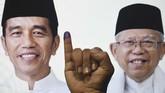 Warga menunjukkan jarinya yang telah dicelupkan ke dalam tinta usai memberikan hak suaranya dengan latar poster Calon Presiden - Calon Wakil Presiden nomor urut 01 Joko Widododan Ma'ruf Amin di Surabaya, Jawa Timur, Rabu (17/4/2019). (ANTARA FOTO/Zabur Karuru)