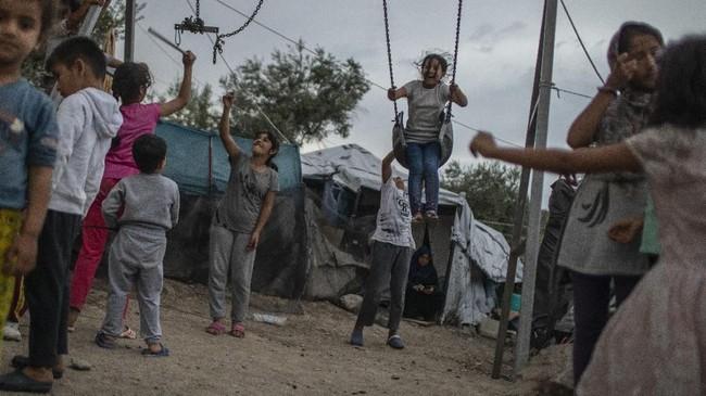 Anak-anak bermain di dekat ayunan di tenda pengungsi Moria di Pulau Lesbos, Yunani pada Jumat (4/10). (AP Photo/Petros Giannakouris)