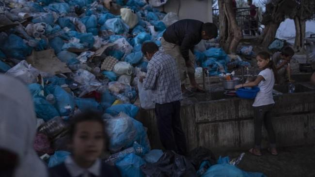 Pengungsi tengah menggunakan pemandian umum di depan tumpukan kantong sampah di tenda pengungsi yang sesak di Pulau Lesbos, Kamis (3/10). (AP Photo/Petros Giannakouris)