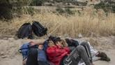 Para pemuda Afghanistan yang tidur karena kelelahan di dekat Kota Madamados, Senin(7/10). (AP Photo/Petros Giannakouris)