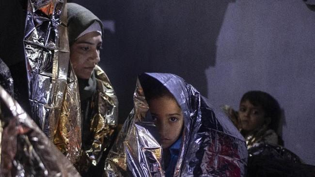Seorang gadis Irak dibungkus selimut termal setelah dipindahkan ke kapal patroli Yunani yang melakukan operasi penyelamatan di dekat Laut Aegea Timur, Kamis (26/9). (AP Photo/Petros Giannakouris)