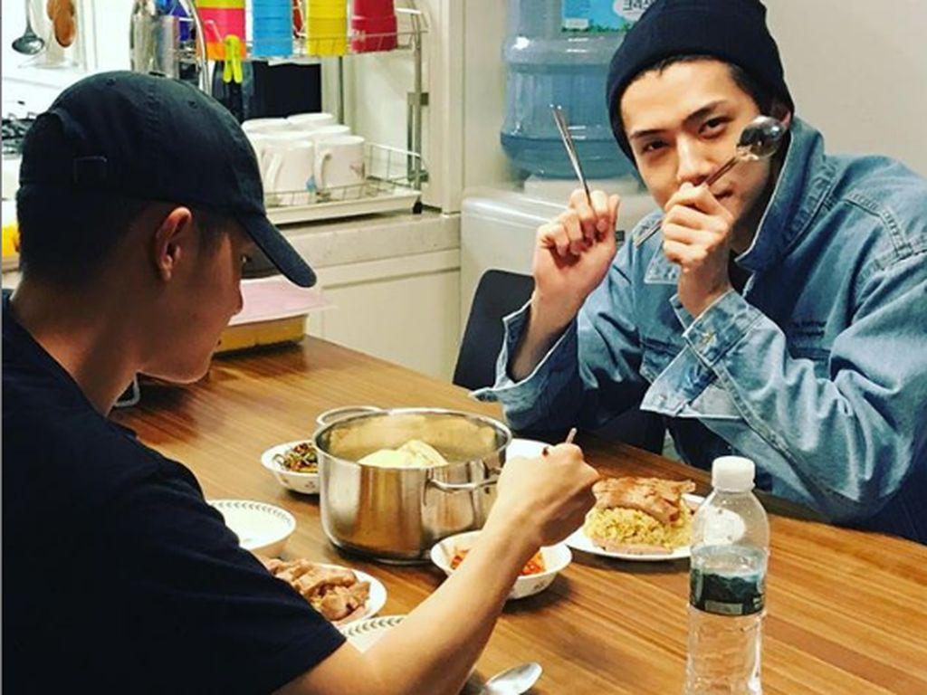 Dengan panci di tengah-tengah meja, Sehun nampak asyik makan nasi dan lauk sambil ditemani temanya. Foto: Instagram @oohsehun