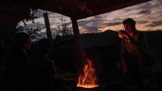 Orang-orang Afghanistan minum teh di tenda pengungsi di Pulau Lesbos, Yunani pada Selasa (8/10)(AP Photo/Petros Giannakouris)