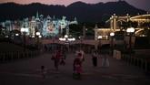 Para pengunjung berjalan pada dini hari di Disneyland Hong Kong. Selama beberapa bulan terakhir Hong Kong terus diterpa gelombang aksi demonstrasi sehingga sektor pariwisata pun terpengaruh. (AP Photo/Felipe Dana)