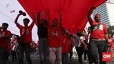 Relawan mengibarkan bendera sepanjang 200 meter untuk pawai menyambut pelantikan Jokowi menjadi Presiden di periode kedua. (CNN Indonesia/Safir Makki)