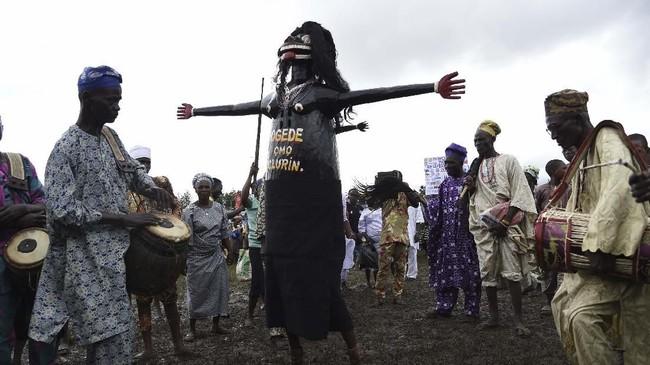 Penari berkostum yang tampil dalam Festival Anak Kembar di Igbo-Ora, Nigeria, pada Sabtu (12/10). (AFP/Pius Utomi Ekpei)