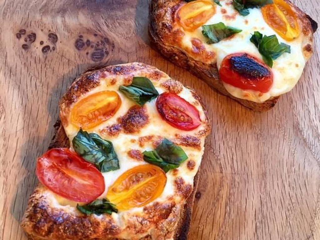 Irisan tomat ceri dan daun basil bisa jadi paduan yang pas buat roti panggang dengan taburan keju mozzarella. Nikmati gurih mulurnya. Foto Instagram @flona_dawson