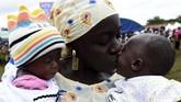 Seorang ibu menciumi dua anaknya yang kembar dalam festival anak kembar di Igbo-Ora, Nigeria.(AFP/Pius Utomi Ekpei)