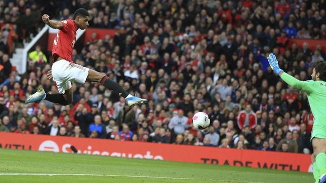 Marcus Rashford mencetak gol ke gawang Liverpool yang dikawan Alisson Becker pada menit ke-36.MU gagal mempertahankan keunggulan dan harus puas dengan skor 1-1 setelah Adam Lallana mencetak gol pada menit ke-85.(AP Photo/Jon Super)