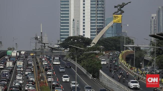 Beberapa aktivis dari Greenpeace Indonesia memasang spanduk berisikan pesan yang ditujukan kepada Presiden Joko Widodo di Patung Dirgantara, Pancoran, Jakarta, Rabu, 23 Oktober 2019. (CNN Indonesia/Bisma Septalisma)