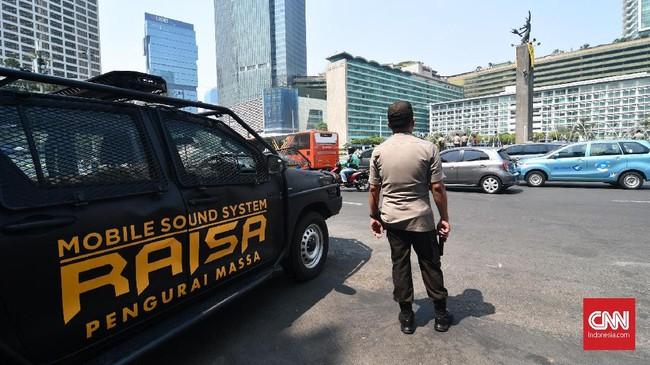 Anggota polisi melihat spanduk raksasa yang terbentang di Patung Selamat Datang, kawasan Bundaran HI, Jakarta Pusat, Rabu (23/10). (CNN Indonesia/ Daniela Dinda)