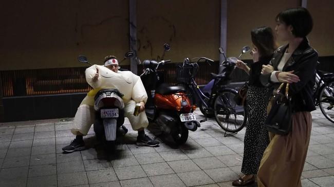 Di Oita, Jepang, para pejalan melihat seorang penggemar rugbi berdandan sebagai pegulat sumo. (AP Photo/Christophe Ena)