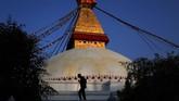 Seorang sesepuh Nepal berjalan melewati stupa Boudhanath di Kathmandu, Nepal. Stupa tua ini merupakan salah satu yang terbesar di dunia dan juga tempat berziarah penting bagi pemeluk agama Buddha, serta situs kebudayaan UNESCO. (AP Photo/Niranjan Shrestha)