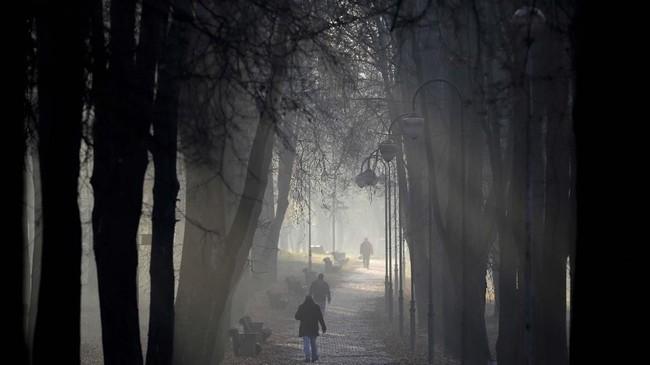 Orang-orang berjalan menerobos pagi yang berkabut di suatu taman di Minsk, Belarusia. (AP Photo/Sergei Grits)