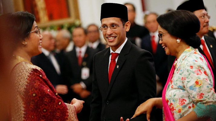 Newly appointed Indonesian Education and Culture Minister Nadiem Makarim, co-founder and ex-chief executive of ride-hailing and payments firm Gojek, reacts as he talks with Indonesian Finance Minister Sri Mulyani and Indonesian Foreign Minister Retno Marsudi, before taking their oaths during the inauguration at the Presidential Palace in Jakarta, Indonesia, October 23, 2019. REUTERS/Willy Kurniawan