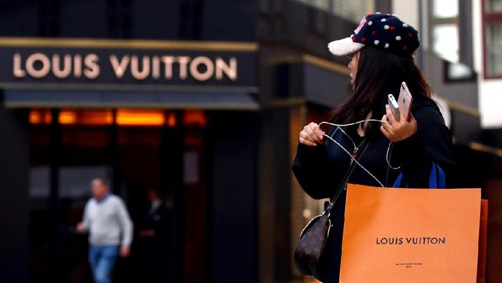 ILE PHOTO: A woman with a Louis Vuitton-branded shopping bag looks towards the entrance of a branch store by LVMH Moet Hennessy Louis Vuitton in Vienna, Austria October 4, 2018. REUTERS/Lisi Niesner