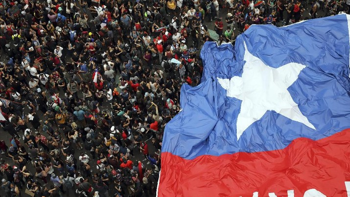 People gather during an anti-government protest in Santiago, Chile, Friday, Oct. 25, 2019. At least 19 people have died in the turmoil that has swept the South American nation. The unrest began as a protest over a 4-cent increase in subway fares and soon morphed into a larger movement over growing inequality in one of Latin America's wealthiest countries. (AP Photo/Rodrigo Abd)