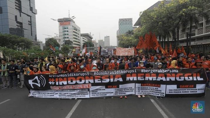 Massa membawa bendera Indonesia dan spanduk bertuliskan kritik untuk Presiden Joko Widodo dan Wakil Presiden Ma'ruf Amin.