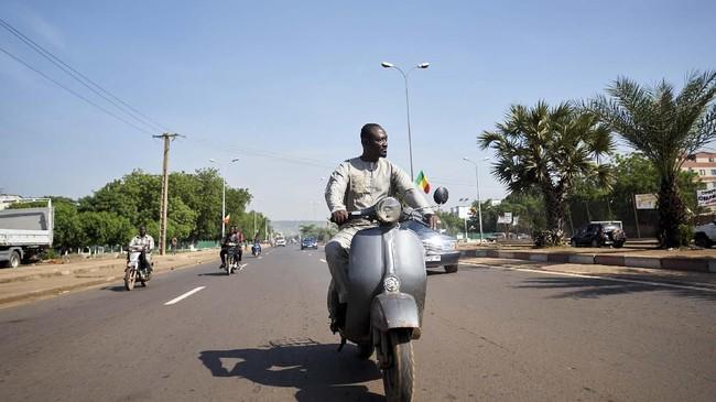 Seydou Seck mengendarai Vespa yang usianya sudah 40 tahun, namun ia mengendarainya dengan tegap dan bangga di ibu kota Mali, Bamako. (MICHELE CATTANI / AFP)