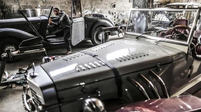 Pria berusia 40 tahun ini kesulitan mendapat suku cadang yang dia butuhkan buat merestorasi mobil tua, maka itu diputuskan perbaikan dilakukan sendiri. (MAHMUD HAMS / AFP)
