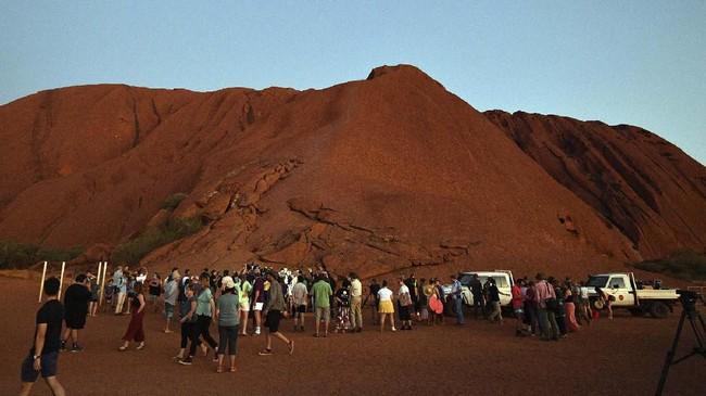 Pendakian terakhir pekan kemarin. Larangan yang pertama kali diumumkan pada tahun 2017 ini telah lama diminta Anangu, Suku Aborigin yang mendiami tanah tersebut, yang memiliki hubungan dengan situs puluhan ribu tahun lamanya. (AFP/Saeed Khan)
