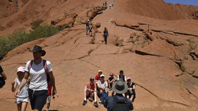 Ada banyak papan larangan di dasar bukit batu yang meminta pengunjung tidak memanjat. Namun larangan ini tak diindahkan oleh pengunjung, terutama setelah aturan baru bakal diterapkan. (AFP/Saeed Khan)