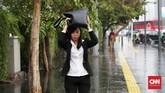 Seorang perempuan mencoba melindungi kepalanya dari curah hujan dengan menggunakan tasnya di kawaasn MH Thamrin, Jakarta, 1 November 2019. Hujan yang terjadi mendinginkan suhu Jakarta yang terpapar terik matahari beberapa bulan ini. (CNN Indonesia/ Safir Makki)