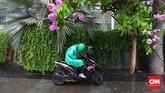 Seorang pengendara sepeda motor berhenti di atas trotoar kawasan MH Thamrin ketika hujan mengguyur ibu kota RI, Jakarta, Jumat, 1 November 2019.(CNN Indonesia/ Safir Makki)