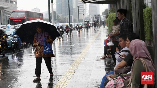 Seorang pejalan kaki melintas dengan payung yang melindunginya dari curah hujan di kawasan MH Thamrin, Jakarta Pusat, sementara yang lain berlindung di bawah atap halte bus. (CNN Indonesia/ Safir Makki)