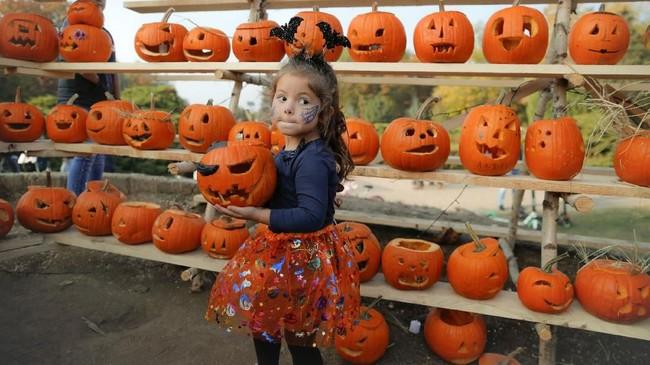 Kota Bucharest di Romania merayakan Halloween dengan festival mengukir labu tahunan yang disebut terbesar di Eropa. Ada 30 ribu labu yang disediakan tahun ini. (AP Photo/Vadim Ghirda)