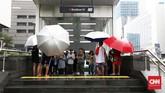 Wargaberlindung dari derasnya hujan di dalam pintu masuk Stasiun MRT Bundaran HI, sementara itusejumlah ojek payung menunggu ada yang menggunakan jasa mereka menembus tumpahan air dari langit, Jakarta, 1 November 2019. (CNN Indonesia/ Safir Makki)