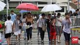 Ojek payung berjalan mendampingi warga yang menggunakan jasa mereka untuk menembus curah hujan di kawasan MH Thamrin, Jakarta Pusat, 1 November 2019. (CNN Indonesia/ Safir Makki)