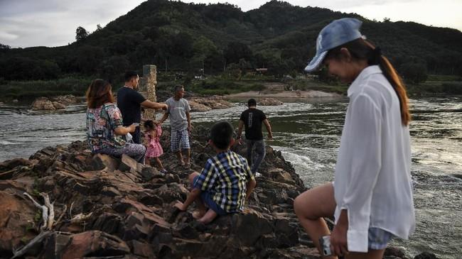 Sungai selebar satu kilometer ini telah menyusut hinggamemunculkan batuan besar dan lapisan yang menutupi genangan air berlumpur.(Photo by Lillian SUWANRUMPHA / AFP)