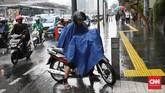 Seorang pengguna sepeda motor menggunakan jas hujan jenis ponco di pinggir jalan saat hujan deras mengguyur kawasan Jakarta, termasuk di Bundaran HI, Jalan MH Thamrin, Jakarta Pusat, 1 November 2019. (CNN Indonesia/ Safir Makki)