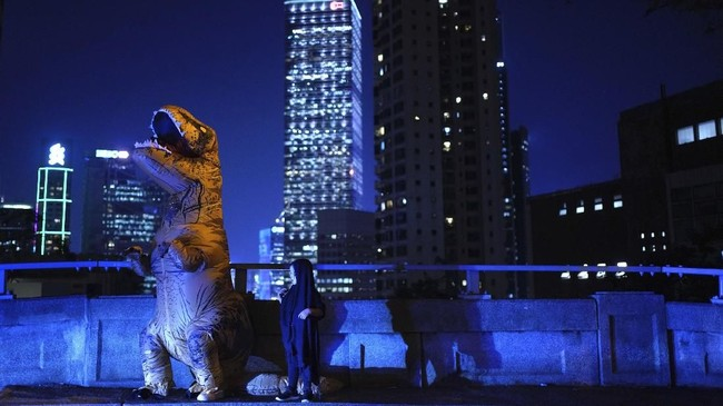 Seorang pria mengenakan kostum dinosaurus dalam perayaan Halloween di Hong Kong. Bersamaan dengan aksi protes, massa demo diminta mengenakan pakaian seram untuk memperingati Halloween selagi berunjuk rasa. (AP Photo/Vincent Yu)