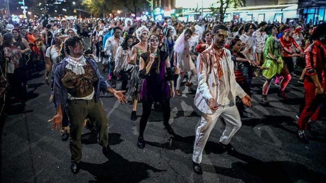 Orang-orang dengan kostum Zombie merayakan Halloween di Sixth Avenue, New York, Amerika Serikat. (AFP/Johannes Eisele)