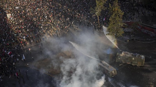 Para pendemo mengepalkan tangan ke udara dan long-march dengan mengibarkan bendera pribumi Chili dan Mapuche untuk menuntut keadilan.(AP Photo/Rodrigo Abd)