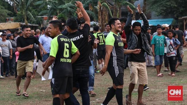Penonton berbaur dengan tim Sparta usai menang penalti dalam laga melawan Putra Betawi. Turnamen tarkam sendiri bisa berlangsung hingga tujuh bulan lamanya dan sering kali digelar setiap akhir pekan. (CNNIndonesia/Safir Makki)