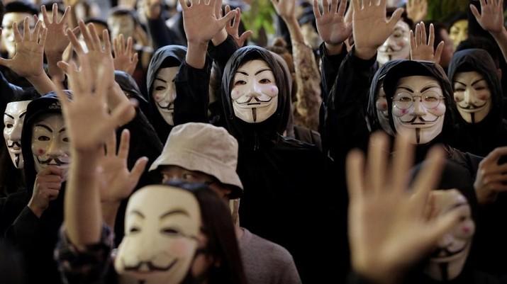 Pengunjuk rasa di Guy Fawkes mengenakan topeng dan mengangkat tangan mereka ketika mereka meneriakkan slogan-slogan selama demonstrasi di Hong Kong.
